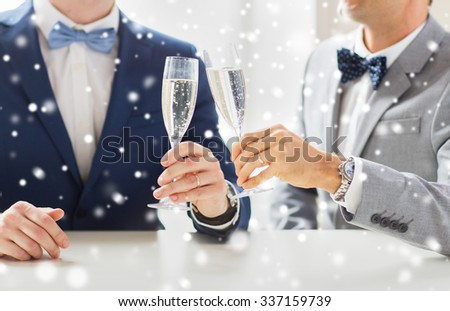 people, celebration, homosexuality, same-sex marriage and love concept - close up of happy married male gay couple in suits and bow-ties drinking sparkling wine on wedding over snow effect - stock photo