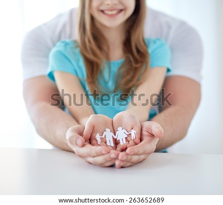people, charity and happiness concept - close up of father and girl holding paper family cutout in cupped hands at home - stock photo