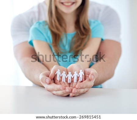 people, charity, demography and family  concept - close up of father and girl holding cutout human in cupped hands at home - stock photo