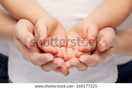 people, charity, family and advertisement concept - close up of woman and girl holding something in empty cupped hands - stock photo