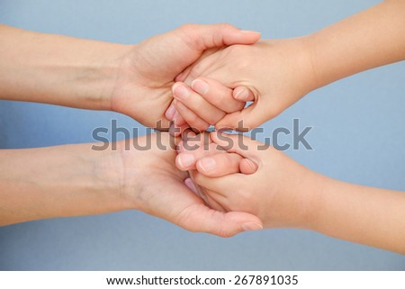 People, charity, family and care concept - close up of woman hands holding girl hands - stock photo