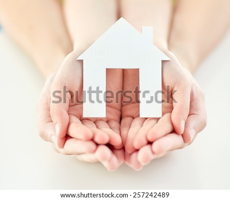 people, charity, family and home concept - close up of woman and girl holding paper house cutout in cupped hands - stock photo