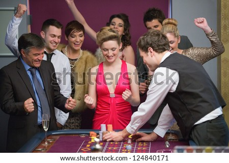 People cheering at roulette table in casino - stock photo