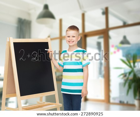 people, childhood, mathematics and education concept - happy little boy with blackboard and chalk writing math exercise over school class room background - stock photo