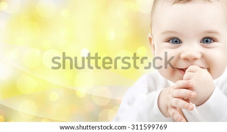 people, children and babyhood concept - close up of of happy baby over yellow background - stock photo