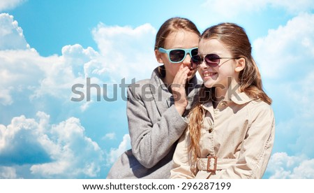 people, children and friendship concept - happy little girl in sunglasses whispering her secret to friends ear or gossiping over blue sky and clouds background - stock photo