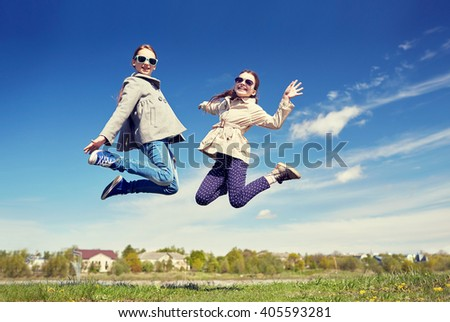 people, children, friends and friendship concept - happy little girls jumping high outdoors - stock photo