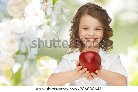 people, children, healthy eating and food concept- happy girl holding red apple over summer or spring garden background - stock photo