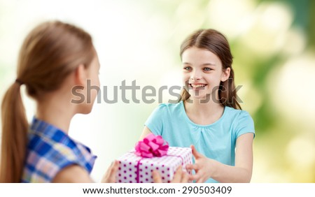 people, children, holidays, friends and friendship concept - happy little girls with birthday present over green background - stock photo