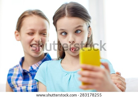 people, children, technology, friends and friendship concept - happy little girls taking selfie with smartphone and having fun at home - stock photo