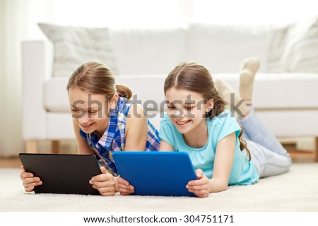 people, children, technology, friends and friendship concept - happy little girls with tablet pc computers lying on floor at home - stock photo