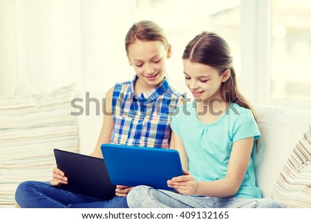 people, children, technology, friends and friendship concept - happy little girls with tablet pc computers sitting on sofa at home