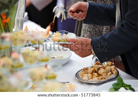 People choosing food from table on buffet party on wedding - stock photo