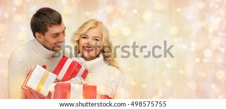 people, christmas, holidays and new year concept - happy family couple in sweaters holding gifts or presents over holidays lights and snow background