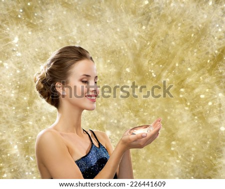 people, christmas, winter holidays and glamour concept - smiling woman in evening dress with diamond over yellow lights background - stock photo