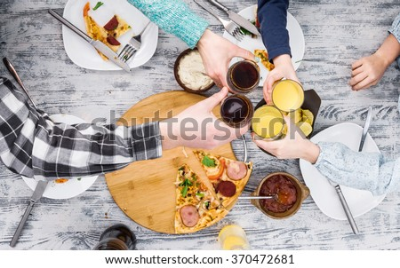 people clanging glasses together having pizza