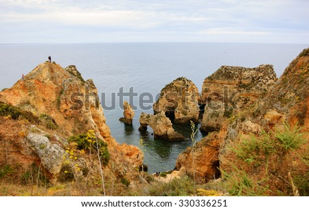 People climbing on the cliffs to see the stone arches, caves and rock formations at Dona Ana Beach (Lagos, Algarve coast, Portugal) in the evening light. A view from above. - stock photo