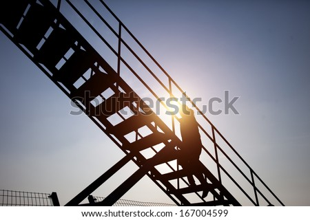 people climbing stairs in sunset on sky background - stock photo