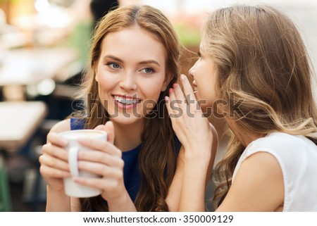 people communication and friendship concept - smiling young women drinking coffee or tea and gossiping at outdoor cafe - stock photo