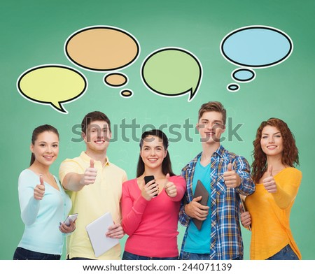 people, communication, school and technology concept - smiling friends with smartphones and tablet pc computers showing thumbs up over green board background with text bubbles - stock photo