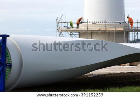 People constructing a wind-turbine - stock photo