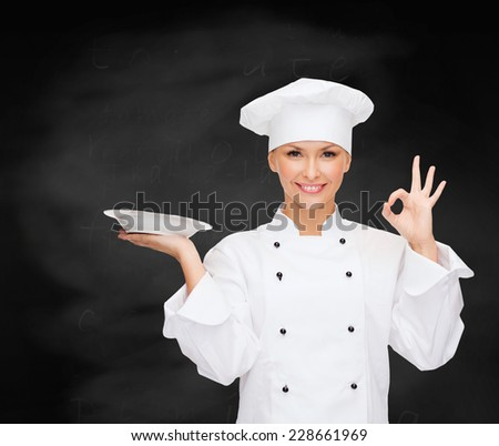 people, cooking and food concept - smiling female chef, cook or baker with empty plate showing ok sign over blackboard background - stock photo