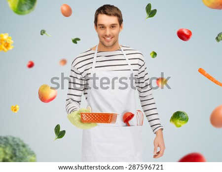 people, cooking, culinary and food concept - happy man or cook in apron with baking and kitchenware over gray background with falling vegetables - stock photo