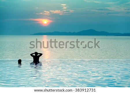 People couple relaxing in infinity pool and beautiful sunset on the sea at twilight times - Blue Tone - stock photo