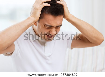 people, crisis, emotions and stress concept - unhappy man suffering from head ache at home