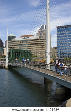 People cross pedestrian bridge, inner harbor, Baltimore, MD