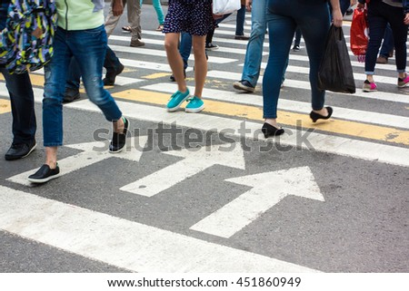 people cross the road at a pedestrian road markings in the rain
