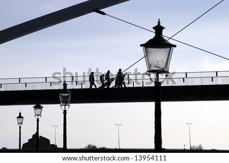 People crossing a bridge - stock photo