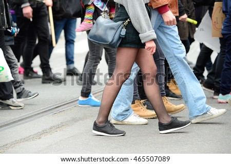 People crossing street, close up of feet. Tram rails