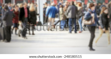People crowd. Intentionally blurred background.