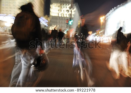 People crowd walking in the city at night (blurred scene) - stock photo
