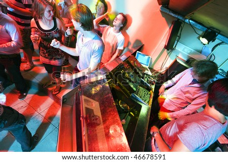 People dancing and flirting near the DJ booth at a nightclub - stock photo