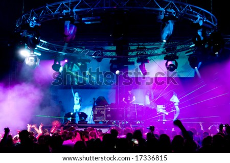 People dancing at the concert, laser show and music - stock photo