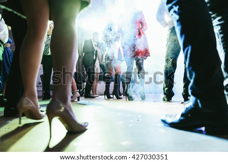 People dancing in the smoke during the wedding party - stock photo