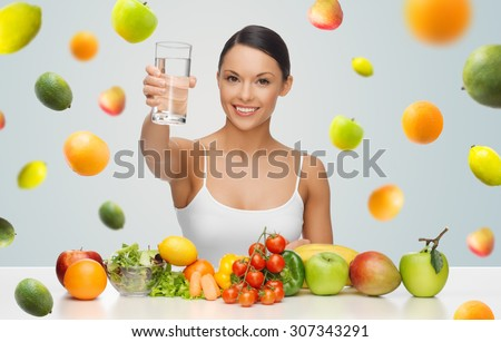 people, diet and vegetarian concept - happy asian woman with healthy food showing glass of water over gray background with falling fruits - stock photo