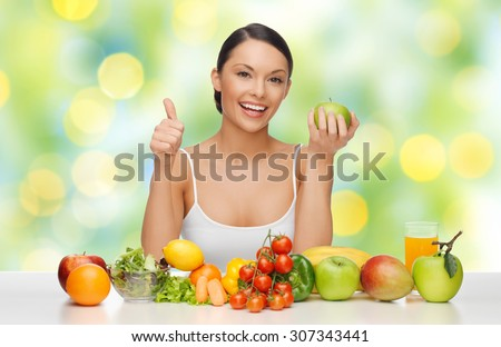people, diet, gesture and vegetarian concept- happy asian woman with healthy food showing thumbs up over green lights background - stock photo