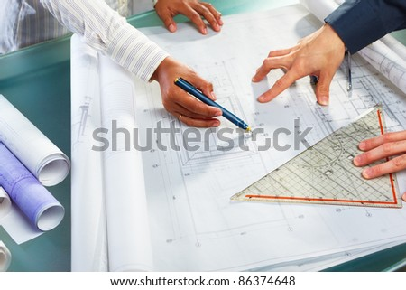 People discussing over architecture design blue print - stock photo