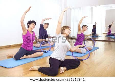 people doing fitness exercises in a gym