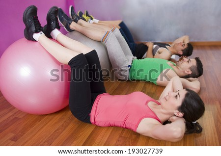 People dong abdmominl exercise with gym ball - stock photo