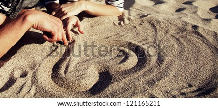 People drawing heart at sand. - stock photo