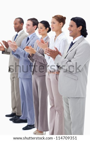 People dressed in suits smiling and applauding while looking towards the left side against white background - stock photo