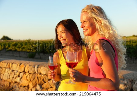 People drinking red rose wine at vineyard. Happy women holding glasses of red wine or rose enjoying a glass outside at sunset. - stock photo