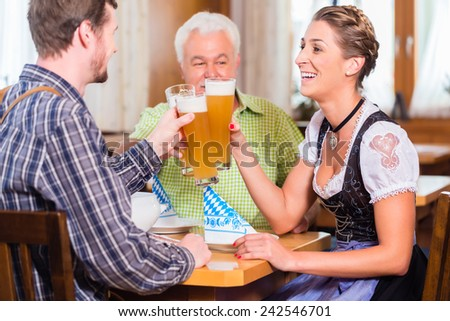 People drinking wheat beer in bavarian restaurant - stock photo