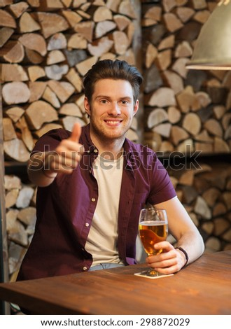 people, drinks, alcohol, gesture and leisure concept - happy young man drinking beer and showing thumbs up at bar or pub