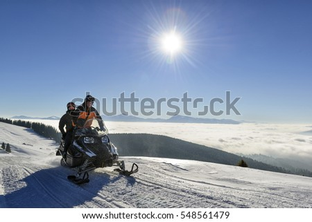 People driving snowmobile for a ride high in the mountains, Bukovel ski resort, Ukraine, December 2016.