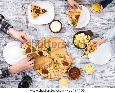 people eating pizza with chips and sauces top view
